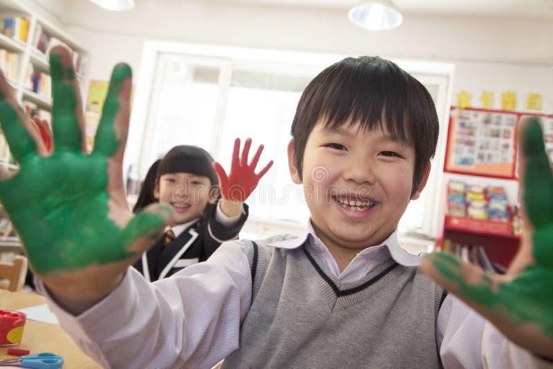 Skolbarn som visar deras täckte händer i målarfärg arkivbild