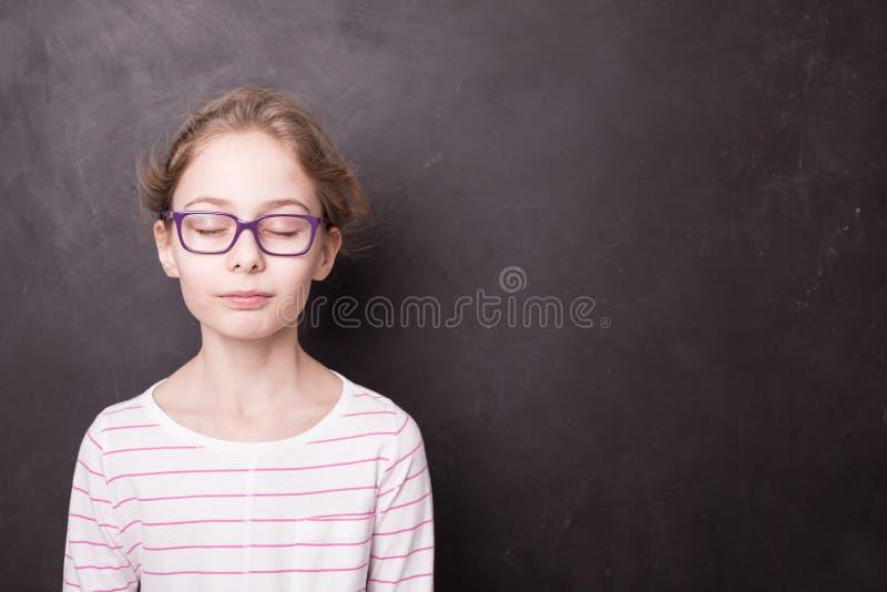 Skolbarnflickan med ögon stängde sig på svart tavla royaltyfria foton