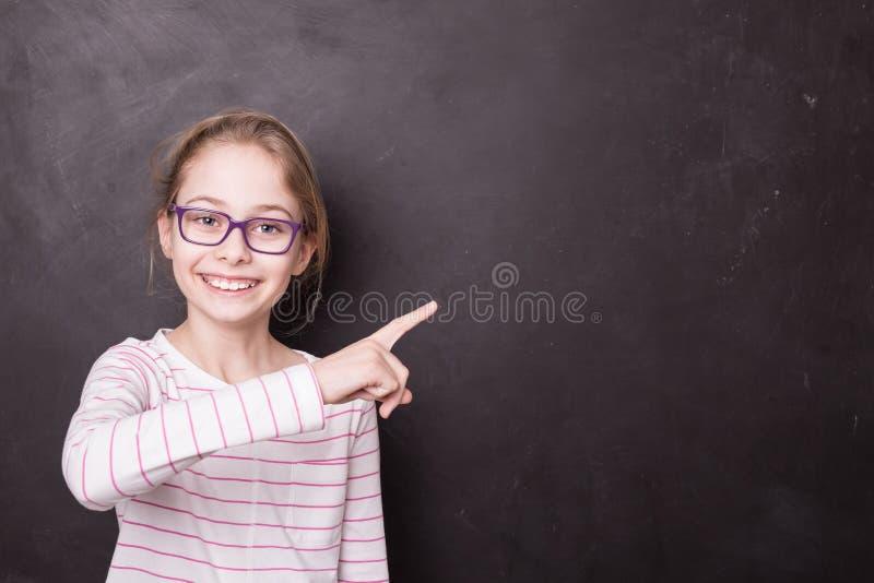 Skolbarnflickaunge, elev som pekar på svart tavla arkivbilder