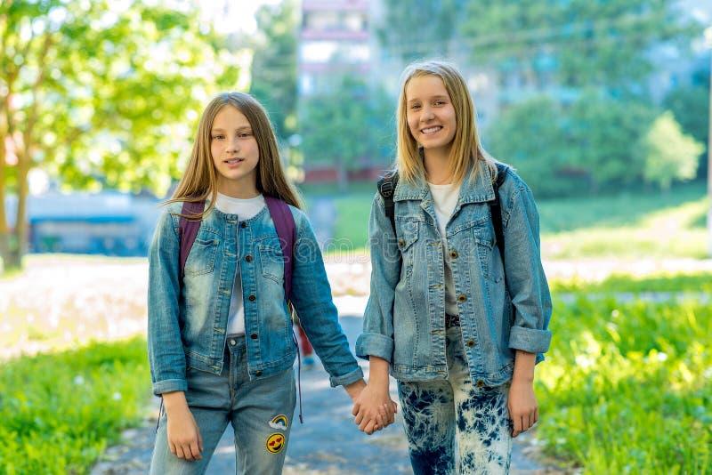 Skolflicka för två flickor Sommar i natur De rymmer sig händer för ` s Begreppsbästa vän, flickvänner sinnesrörelse royaltyfria bilder