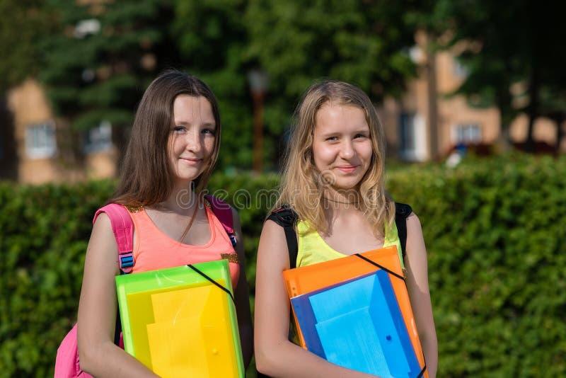 Skolflicka för två flickor Sommar i natur Leende lyckligt Skolmogna kurser I händer av en mapp med anteckningsböcker Honom arkivbild