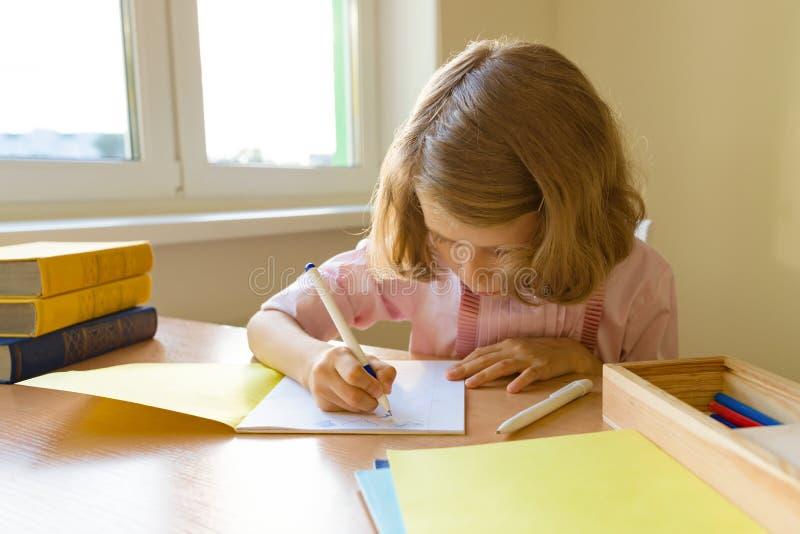 Skolflicka flicka av 8 år som sitter på tabellen med böcker och skriver i anteckningsbok Skola, utbildning, kunskap och barn arkivfoton