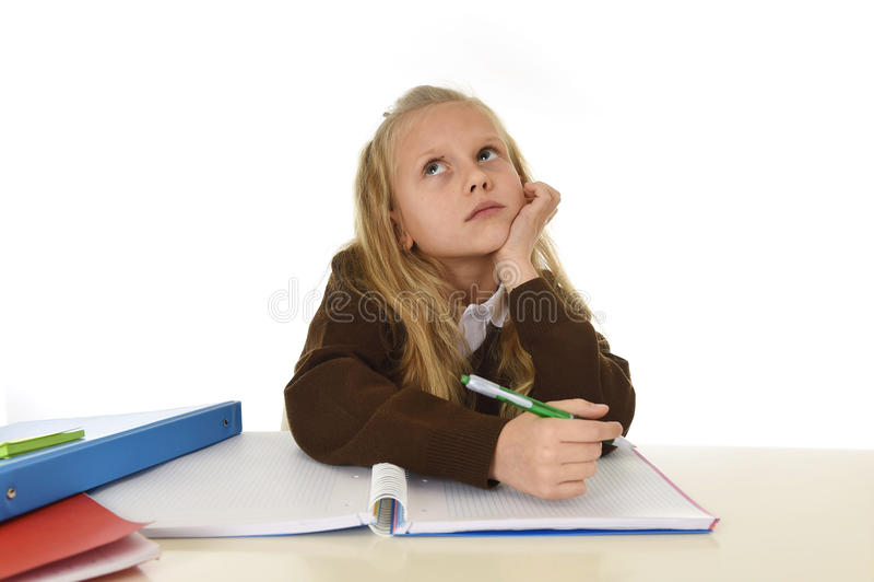 Skolflicka i sammanträde för skolalikformig på att studera skrivbordet som gör läxa som ser fundersam och frånvarande mening royaltyfri bild