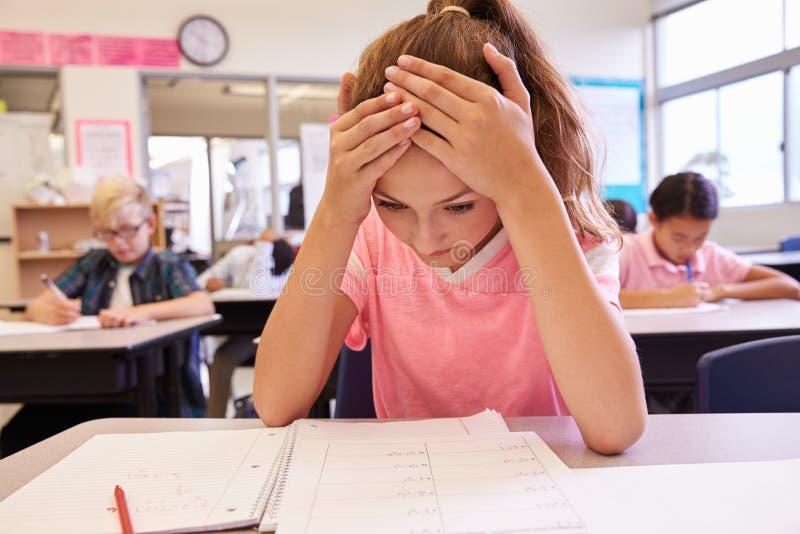 Skolflicka med huvudet i händer i en grundskolagrupp arkivfoto
