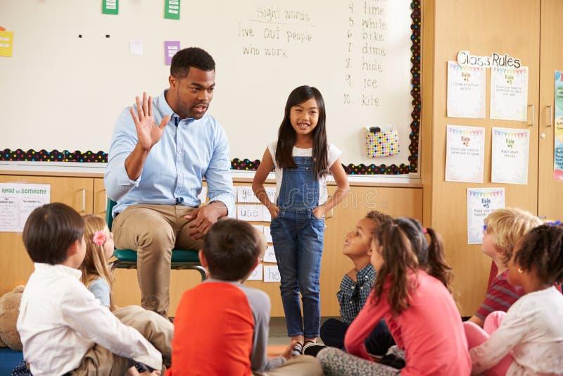 Skolflicka på framdelen av elementär grupp med läraren arkivfoto
