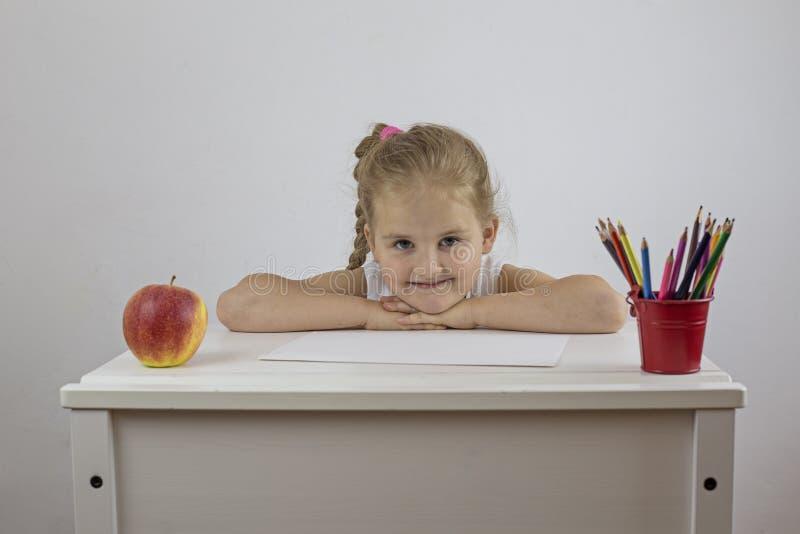 Skolflicka på hennes skrivbord med ett gladlynt ansiktsuttryck fotografering för bildbyråer