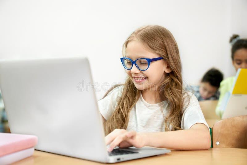 Skolflicka på skrivbordet i klassrumet som arbetar i bärbar dator royaltyfria bilder