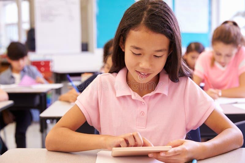 Skolflicka som använder minnestavladatoren i grundskolagrupp royaltyfria bilder