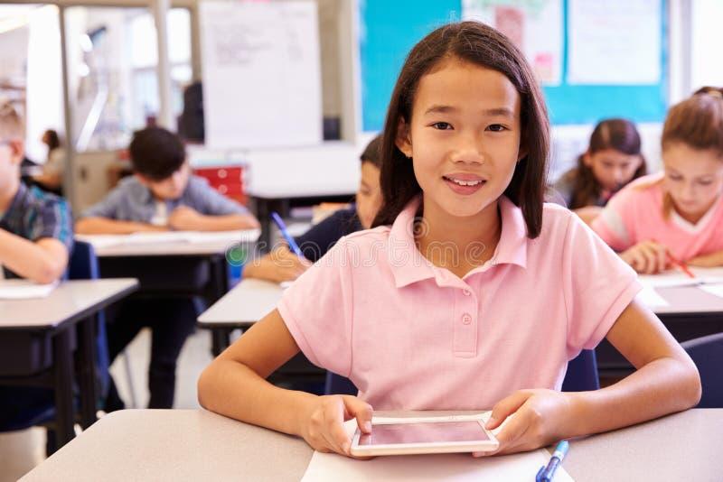 Skolflicka som använder minnestavladatoren i grundskolagrupp fotografering för bildbyråer