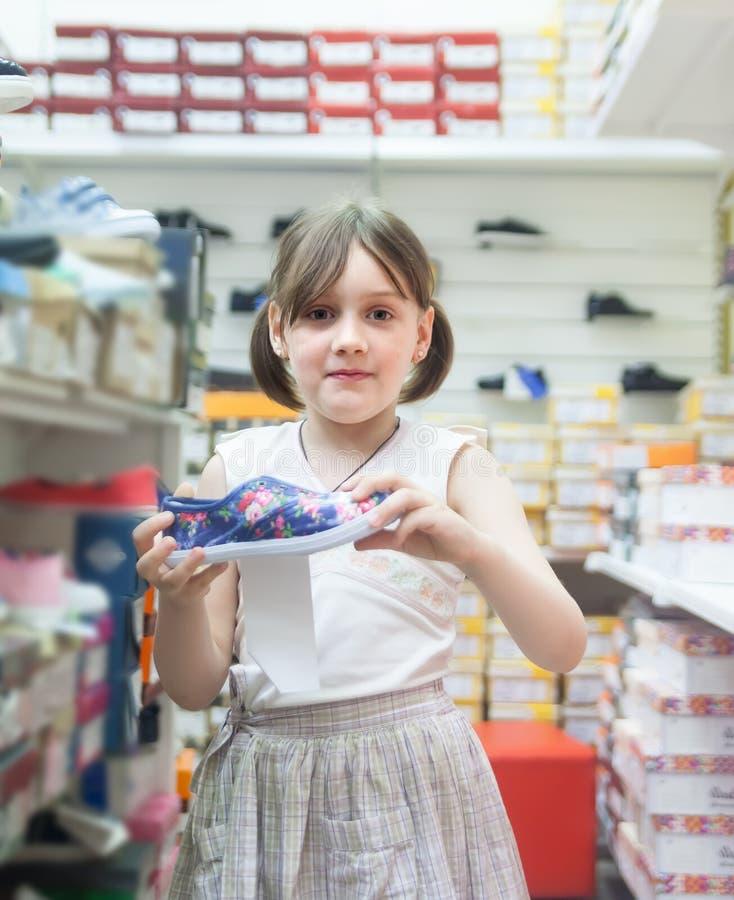 Skolflicka som väljer skor för skola royaltyfri bild