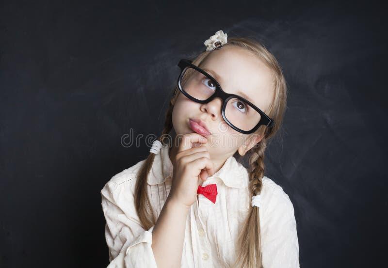 Skolflickabarn som tänker och ser upp tillbaka skola till royaltyfria bilder