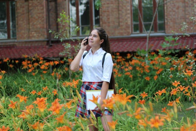 Skolflickaflicka med långt hår i skolalikformig som talar på telefonen arkivfoto