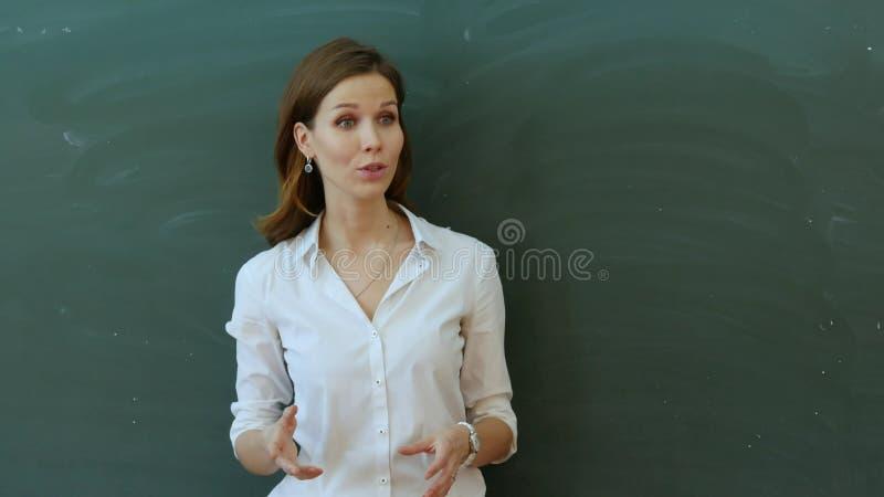 Skolflickahandstil med hennes lärare i ett klassrum royaltyfri fotografi