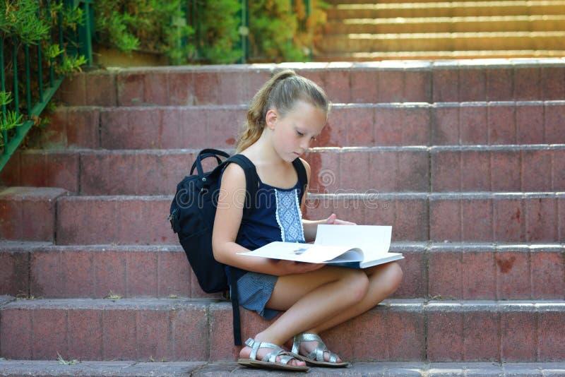 Skolflickan 8 år gammal görande läxa på trappa läser boken royaltyfria foton