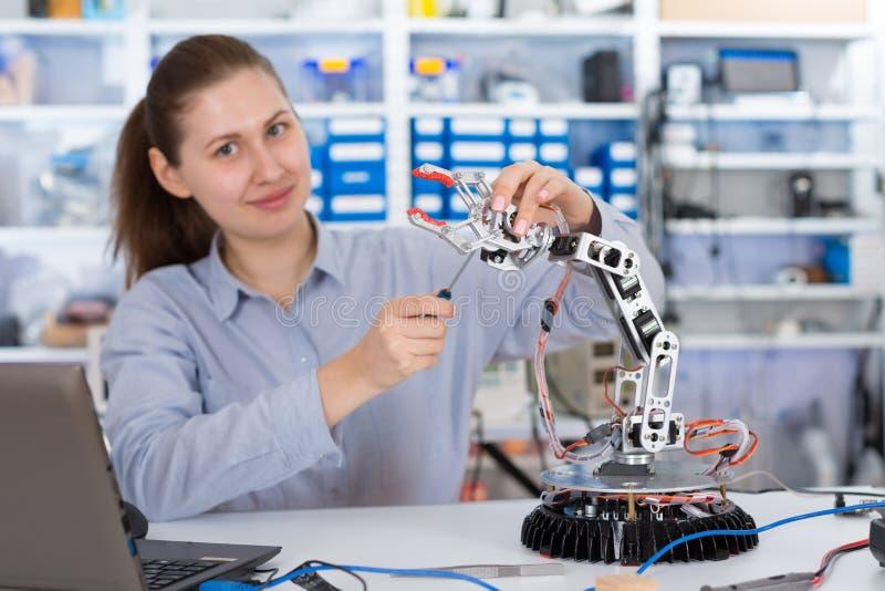 Skolflickan justerar robotarmmodellen royaltyfri fotografi