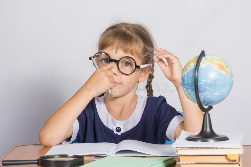 Skolflickan korrigerar exponeringsglas, medan sitta på ett skrivbord i klassrumgeografin royaltyfria foton
