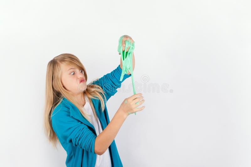 Skolflickan som spelar med grön slam, ser som smörja royaltyfri bild