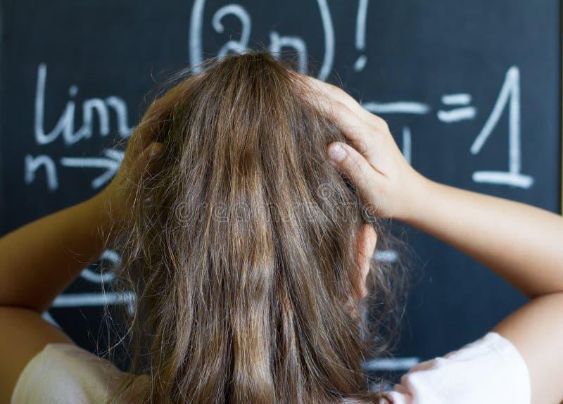 Skolflickan tänker på den svåra uppgiften av matematik fotografering för bildbyråer