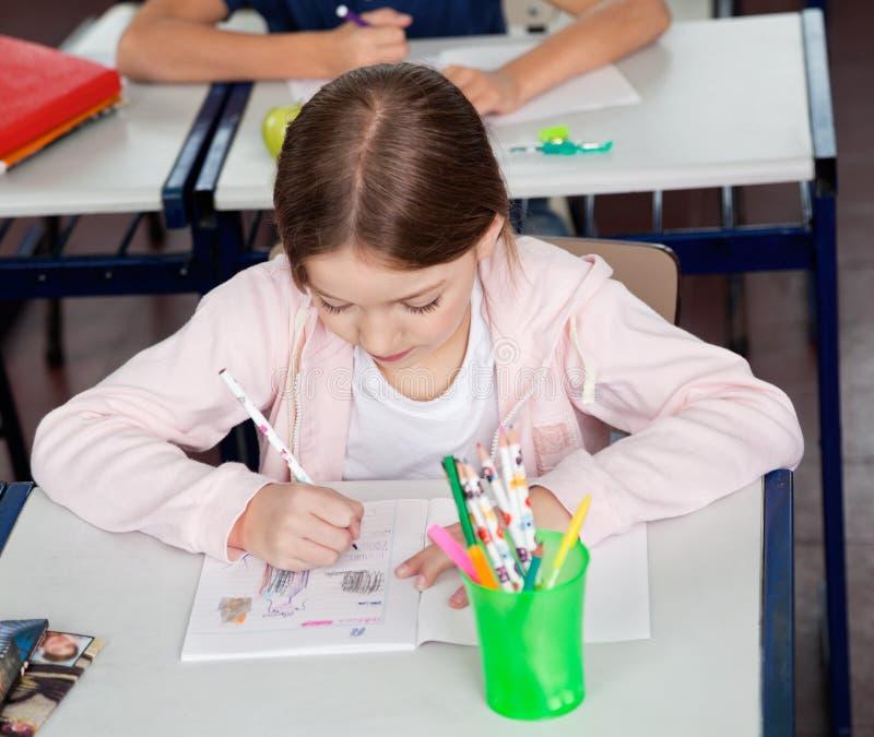 Skolflickateckning på skrivbordet i klassrum royaltyfri bild