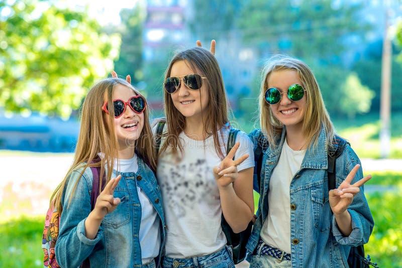 Skolflickatonåring för tre flickor, bärande jeanskläder och solglasögon Lyckligt le med gest av händer som visar Hello arkivbilder
