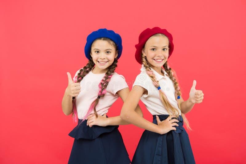 Skolflickor bär formella likformig- och baskerhattar Elitskolahögskola Utbildning utomlands Applicera formen skriver in internati arkivbilder