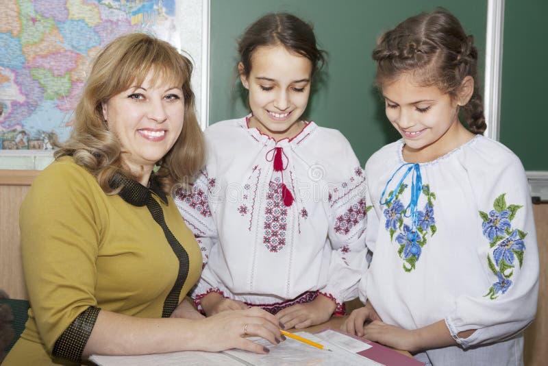 Skolflickor i broderad skjortor och lärare royaltyfri foto