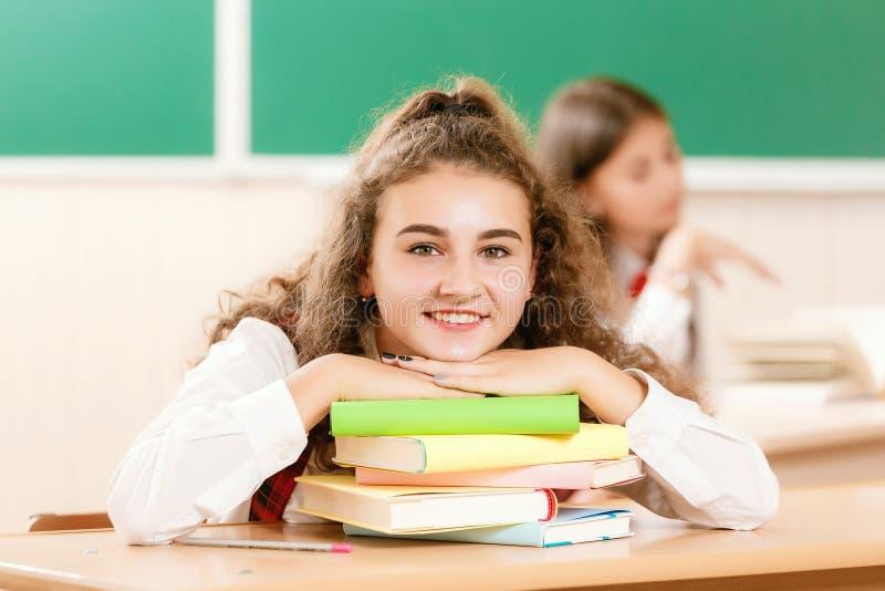 Skolflickor i skolalikformig sitter för par i klassrumet Flickor går till skolan royaltyfri fotografi
