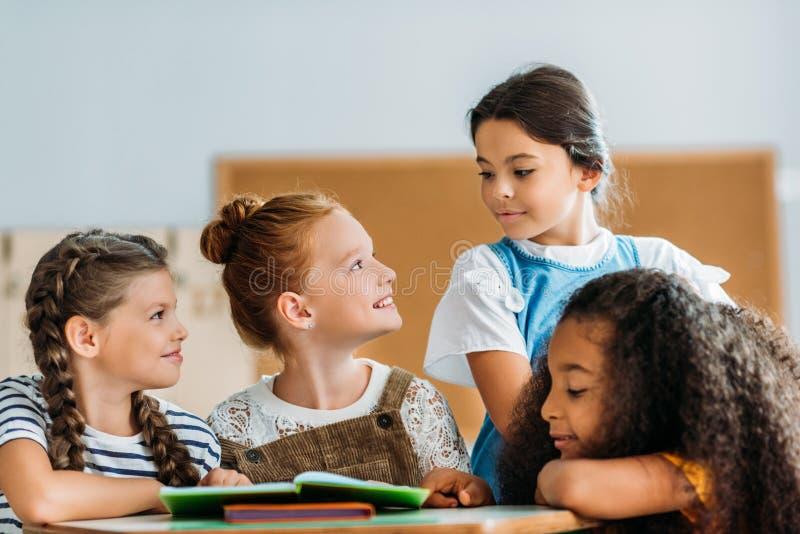 skolflickor som pratar med deras klasskompis under avbrott royaltyfria bilder