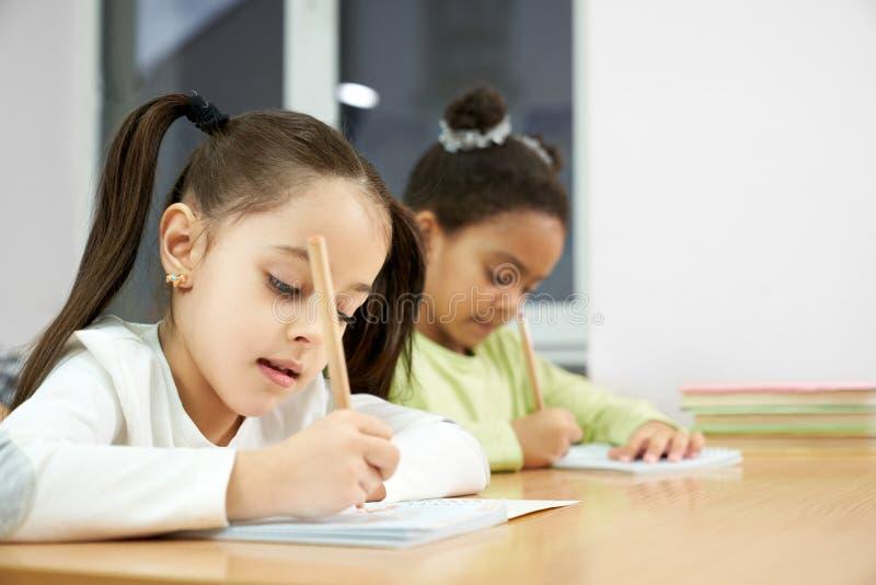 Skolflickor som skriver i förskriftsbok på kursen i klassrum royaltyfri fotografi