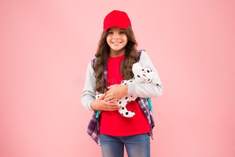 Skolklubb Snygg skolflicka Liten modern cutin med ryggsäck bär med sig mjuk leksakshund Ta med dig en favoritleksak royaltyfri bild