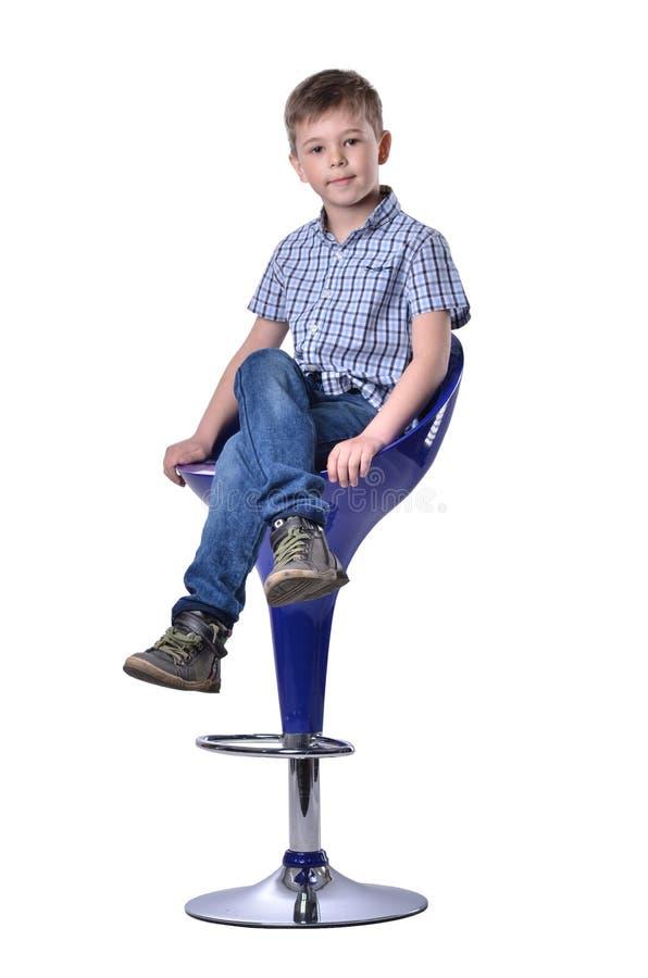 Skolpojke i sammanträde för skjorta för innegrejblått rutigt på högväxt stol royaltyfri foto
