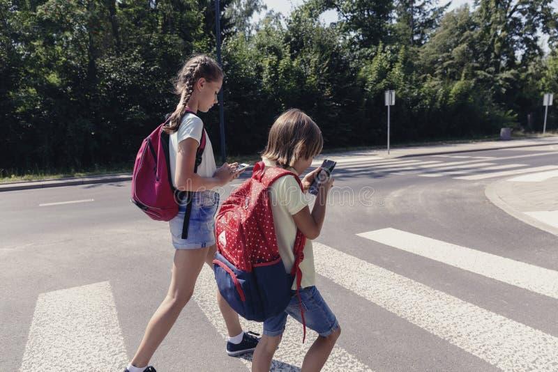 Skolpojke med ryggsäcken och hans tonårs- syster som använder mobiltelefoner på övergångsställe royaltyfria bilder