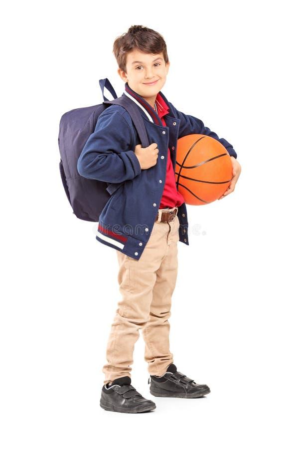 Skolpojke med ryggsäcken som rymmer en basket arkivbild