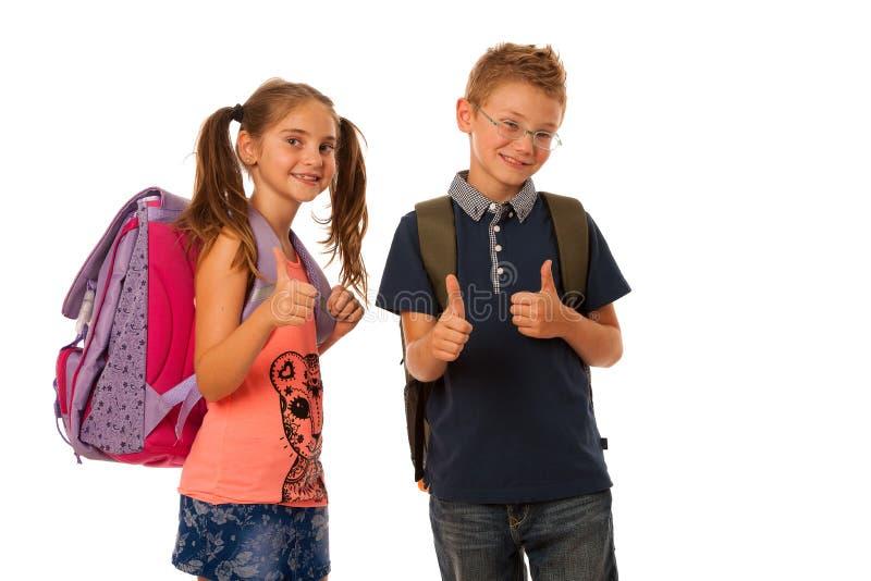 Skolpojke och skolflicka med isolerade skolväskor arkivbild