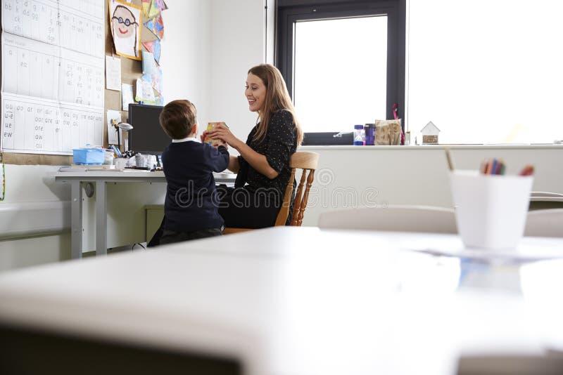 Skolpojke på grundskola för barn mellan 5 och 11 år som framlägger en gåva till hans lärarinna i ett klassrum, selektiv fokus, ti arkivfoto