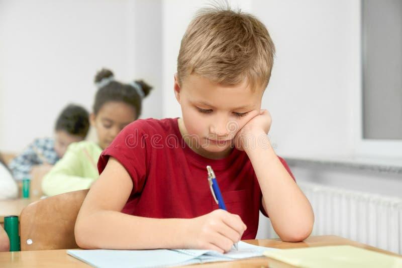 Skolpojke på skrivbordhandstil med pennan i förskriftsbok arkivbilder