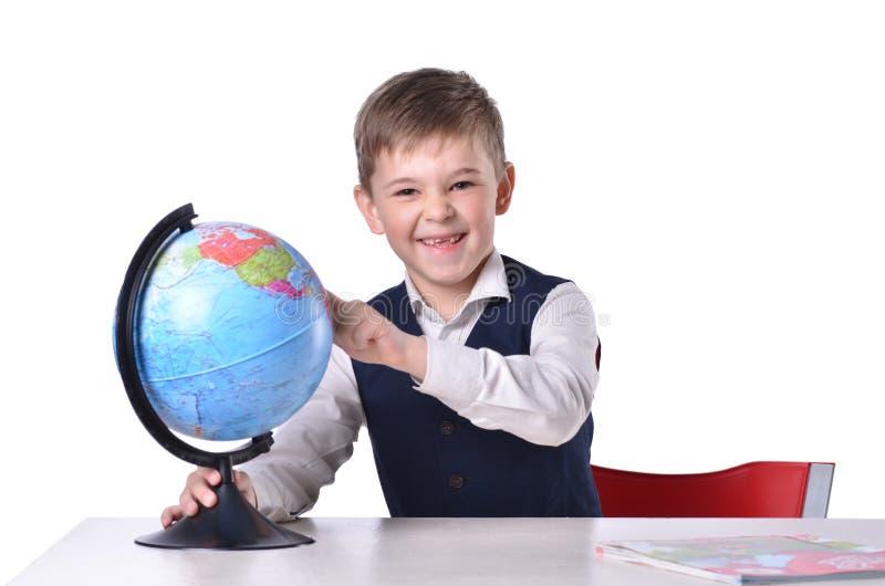 Skolpojke på skrivbordskratten och peka på ett jordklot arkivbild