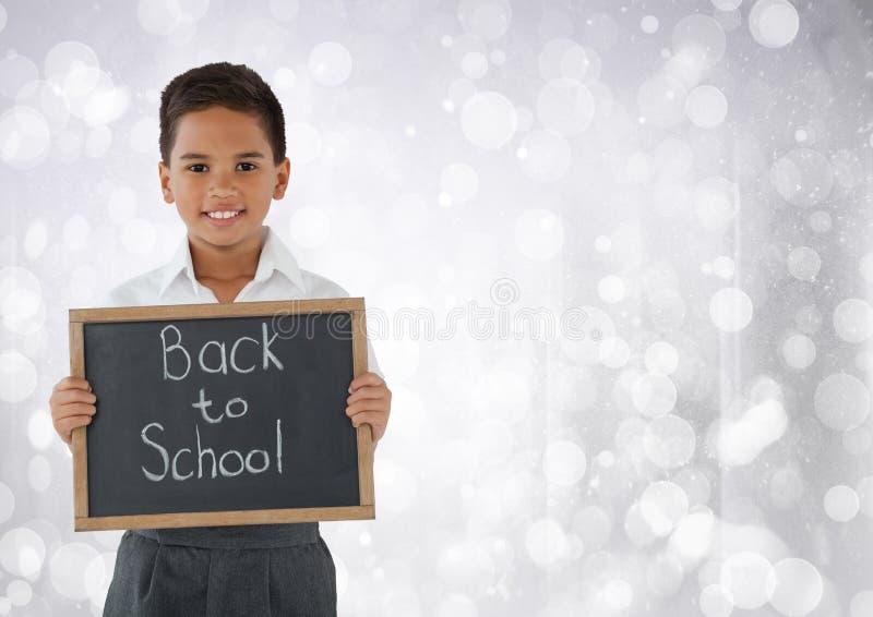 Skolpojke som är hållande tillbaka till skolasvart tavla som är främst av ljus bokehbakgrund royaltyfri fotografi