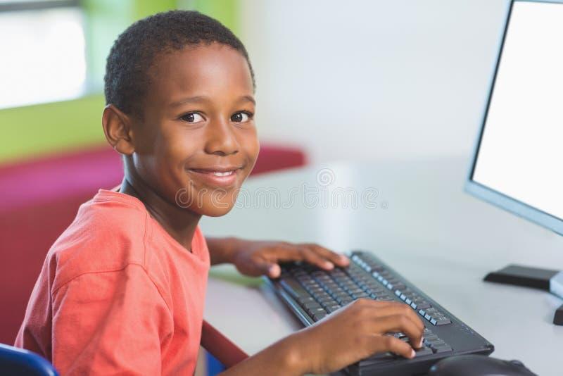 Skolpojke som använder datoren i klassrum royaltyfria foton