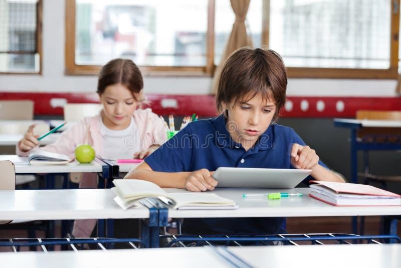 Skolpojke som använder den Digital minnestavlan i klassrum royaltyfri fotografi