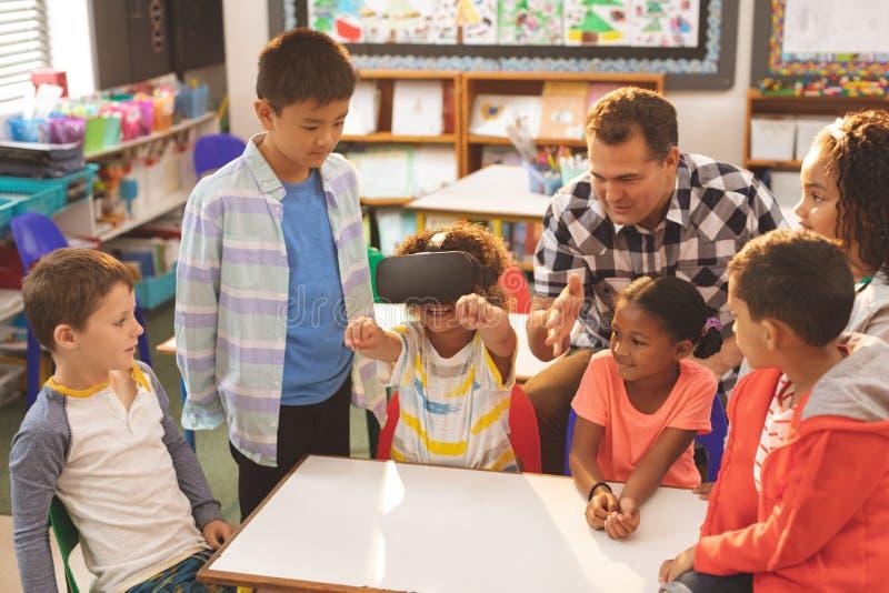 Skolpojke som använder virtuell verklighethörlurar med mikrofon med hans klasskompis och lärare arkivfoto