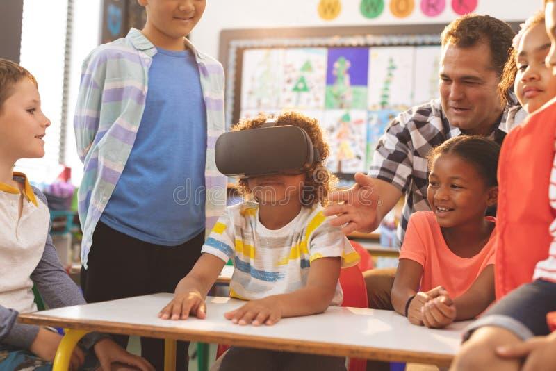 Skolpojke som använder virtuell verklighethörlurar med mikrofon med hans klasskompis och lärare royaltyfri fotografi