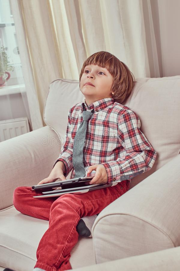 Skolpojke som bär en rutig skjorta med bandet som rymmer en digital minnestavla, medan sitta på en soffa med en konstig blick på arkivfoto