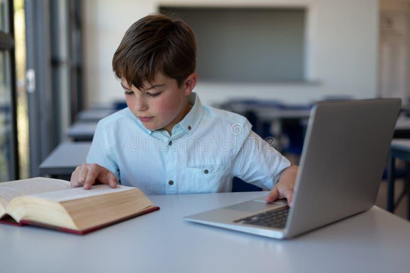 Skolpojke som läser en bok och använder bärbara datorn i ett klassrum arkivfoto