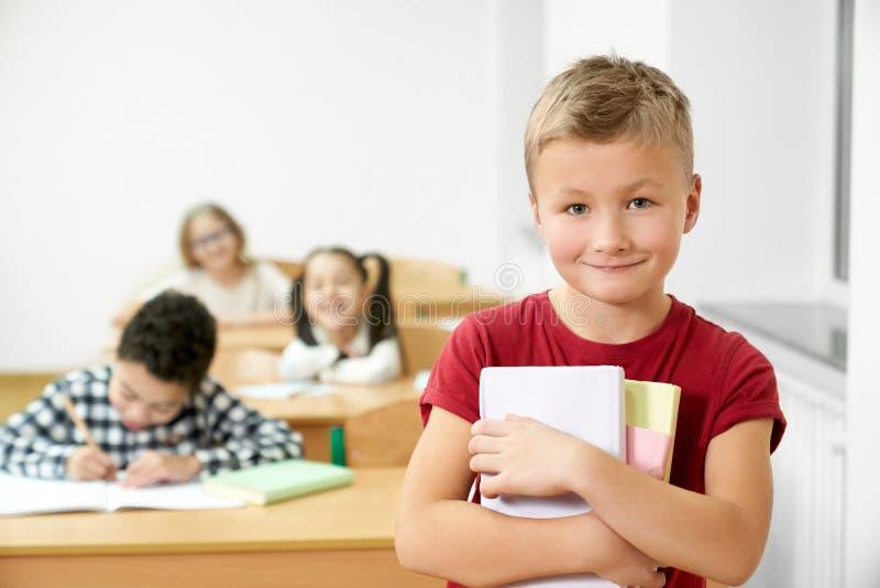 Skolpojke som rymmer böcker och att se kameran som ler royaltyfria bilder