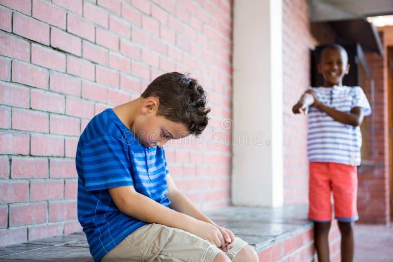 Skolpojke som skrattar på ledsen klasskompis i korridor royaltyfria bilder