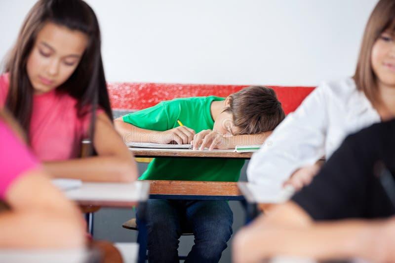 Skolpojke som sover på skrivbordet royaltyfria bilder