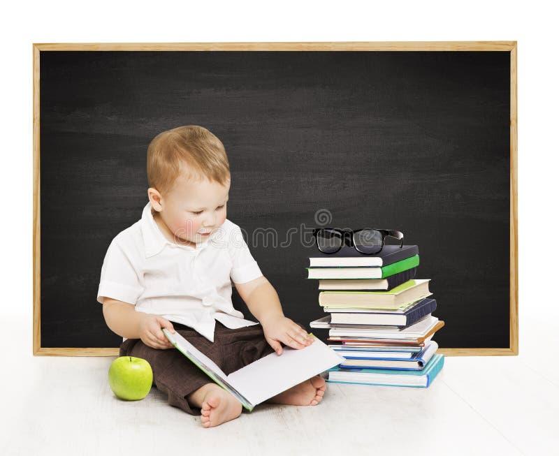 Skolpojkeläsebok nära svart tavla, dagisskolapojke, royaltyfria bilder