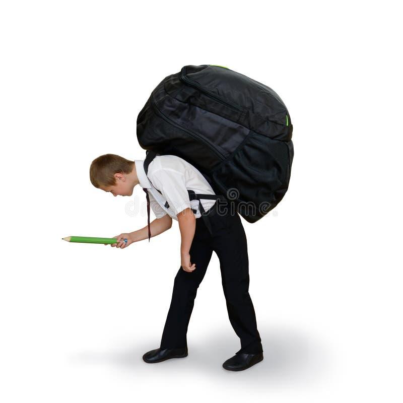 Skolpojken bär en stor ryggsäck royaltyfri foto