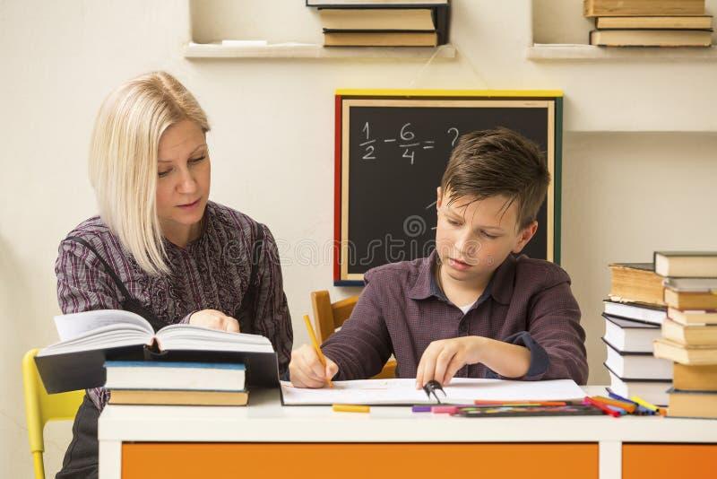 Skolpojken gör förlovad läxa med handleda Hjälp royaltyfri fotografi